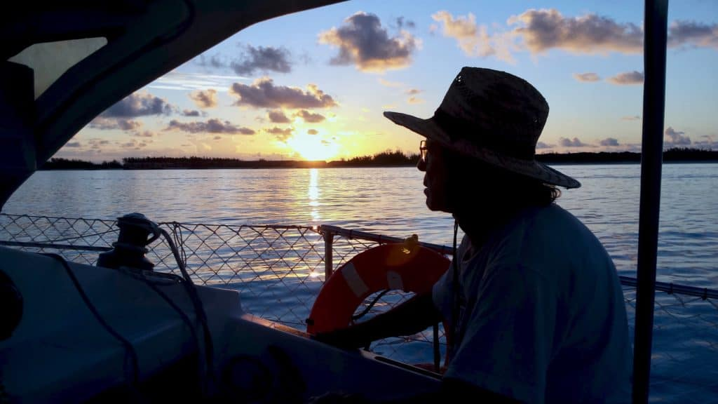 Silhouette of man in hat at anchor during sunset.