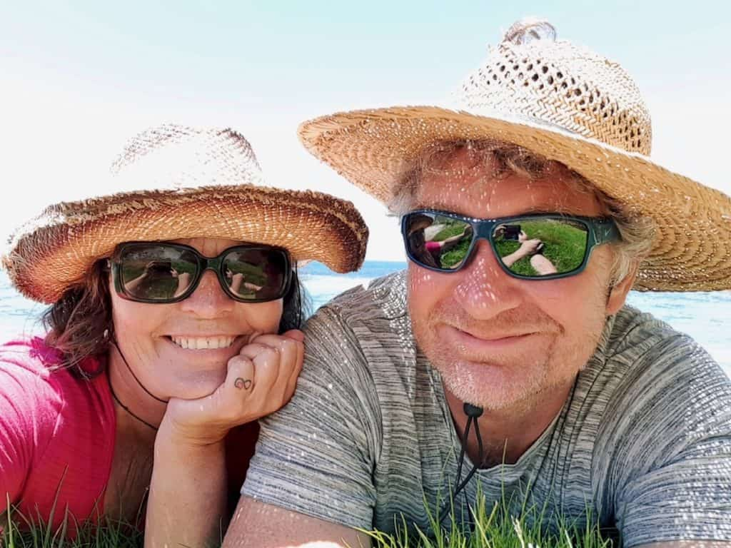 Woman and man in sunglasses and straw hats.